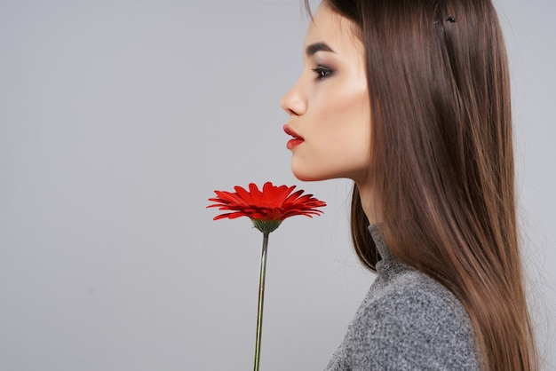 Garota com maquiagem brilhante, flor vermelha, estúdio de luxo