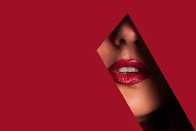Garota com maquiagem brilhante olhando pelo buraco no papel