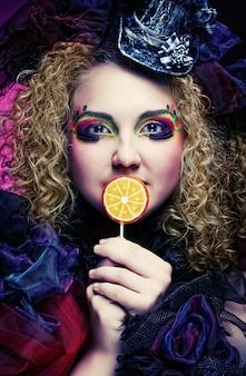 Garota com maquiagem criativa detém pirulito.