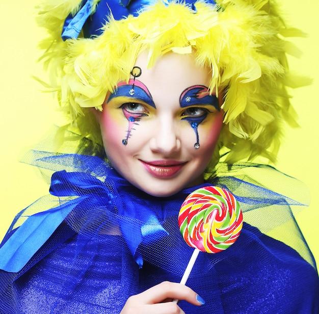 Garota com maquiagem criativa detém pirulito