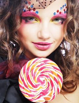 Garota com maquiagem criativa segurando pirulito.