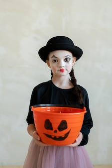 Garota com maquiagem de halloween pedindo guloseimas enquanto olha para você