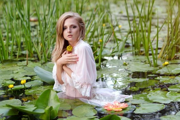 Garota com maquiagem suave no lago entre lótus e nenúfares