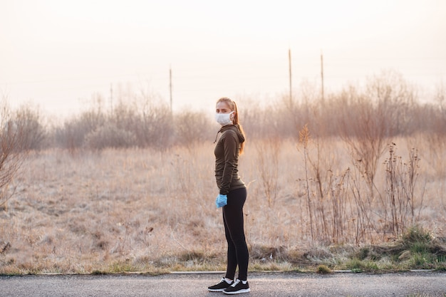 Garota com máscara e luvas azuis durante a quarentena saiu para correr