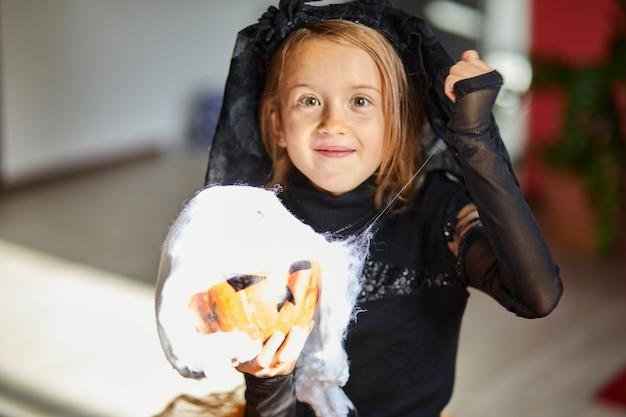 Garota com máscara em casa com fantasia de halloween com abóbora jack ou laurent