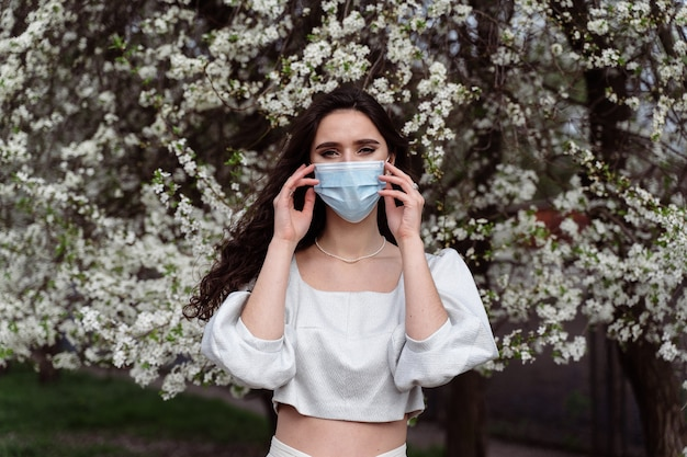 Garota com máscara médica perto de árvores florescendo brancas no parque. caminhar ao ar livre no campo durante o período de quarentena do coronavírus covid-19. estilo de vida na primavera.