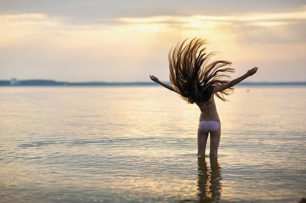 Garota com o cabelo solto no mar durante o pôr do sol