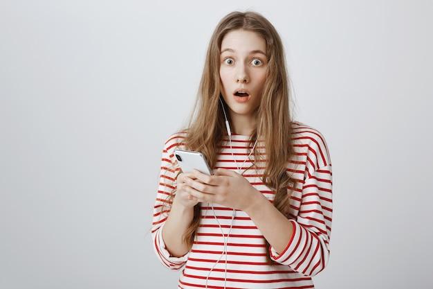 Garota com o queixo caído, assustada e chocada, lendo algo online pelo celular