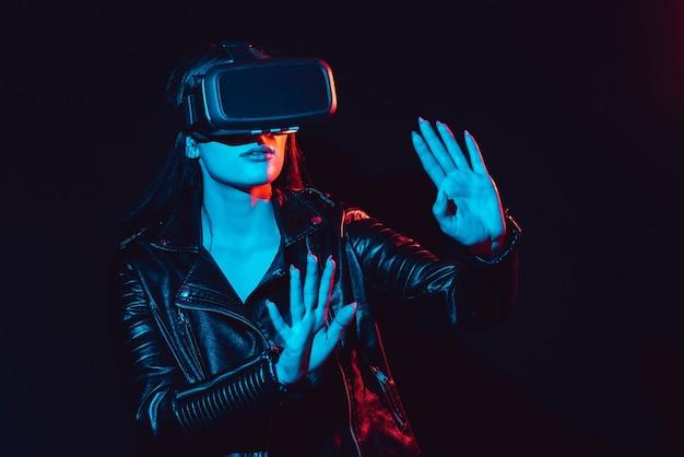 Garota com óculos de realidade virtual está imersa em realidade aumentada com a ajuda de tecnologias modernas e inovadoras