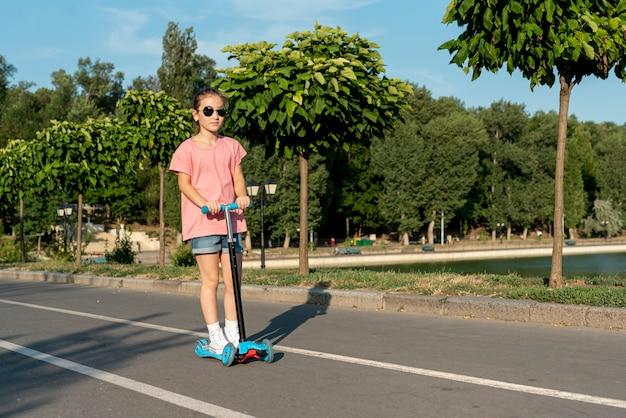 Garota com óculos de sol, andar de scooter
