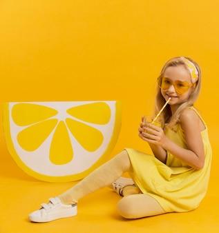 Garota com óculos de sol posando com decoração de fatia de limão