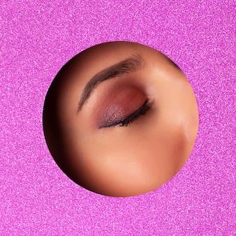 Garota com olhos brilhantes compõem parece através do buraco no papel violeta