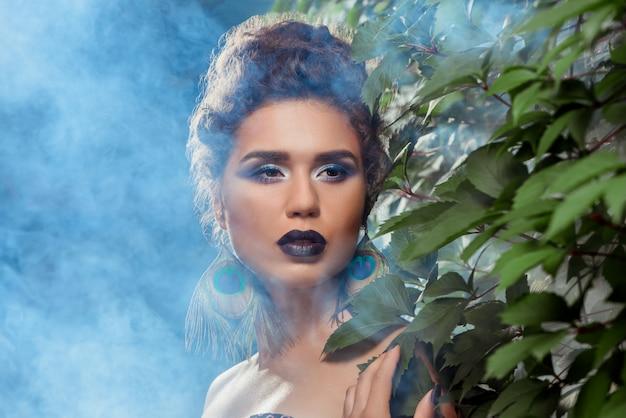 Garota com os lábios roxos escuros, olhos brilhantes e brincos feitos de penas de pavão.
