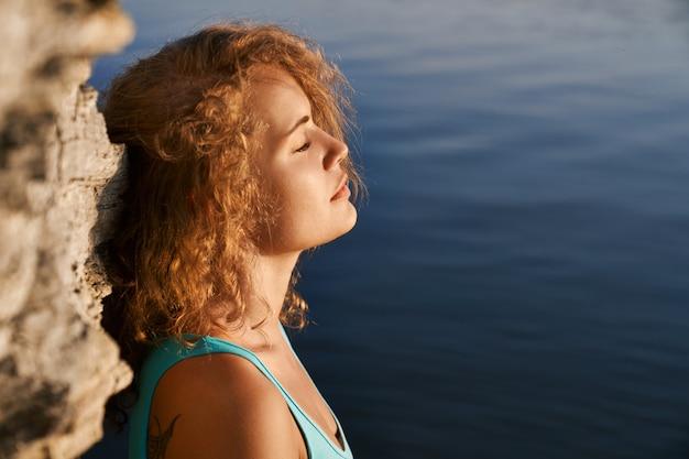 Garota com os olhos fechados, meditando perto de pedra e água.