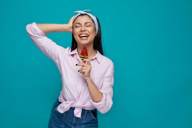 Garota com os olhos fechados, posando, segurando pirulito de melancia.