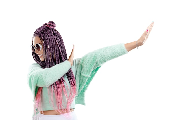 Garota com penteado de tranças rosa em roupas turquesa e óculos de sol isolam em um fundo branco. conceito de estilo moderno, inclusividade, copie o espaço.