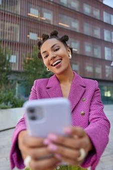 Garota com penteado teendy vestida com jaqueta rosa posa para selfie na câmera do smartphone faz passeios com celulares modernos em ambiente urbano vai passear