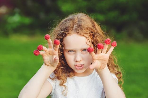 Garota com raiva com framboesas nos dedos dela.