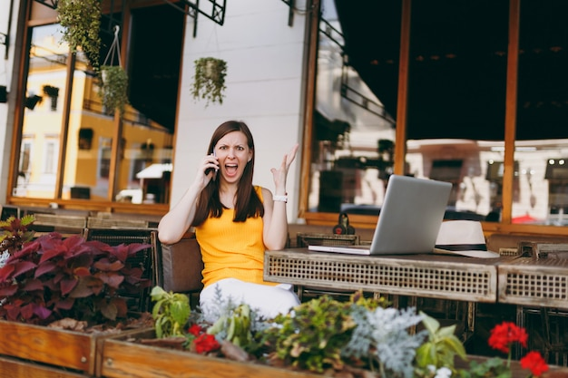 Garota com raiva em um café de rua ao ar livre, sentada à mesa com um computador laptop, falando no celular, gritando e perturbando o problema, no restaurante durante o tempo livre
