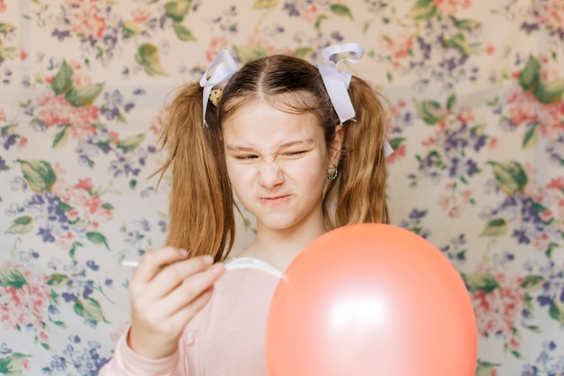 Garota com raiva estourando balão com garfo