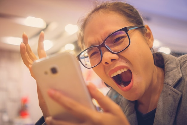 Garota com raiva no telefone, boca aberta ela lê uma mensagem de texto