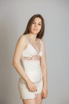 Garota com roupa íntima clara em fundo cinza