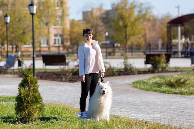 Garota com roupas brancas com um grande cachorro branco