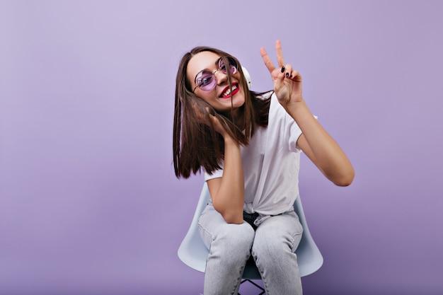 Garota com roupas brancas da moda, posando com o símbolo da paz, enquanto ouve música. mulher deslumbrante em fones de ouvido e óculos de sol sorrindo.