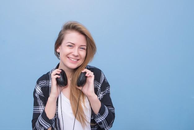 Garota com roupas casuais e fones de ouvido no pescoço sobre um fundo azul, olhando para a câmera e sorrindo.