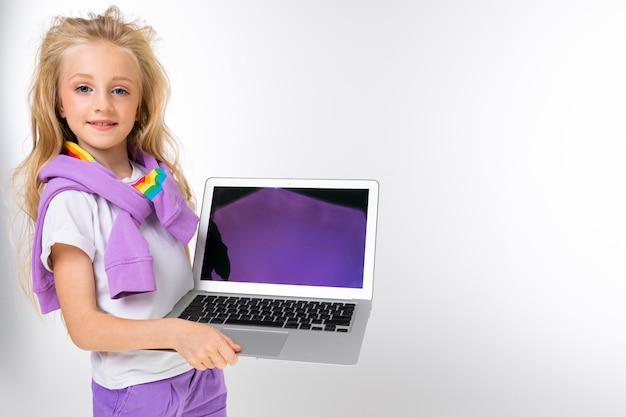 Garota com roupas casuais, segurando um laptop com uma maquete nas mãos em uma parede branca