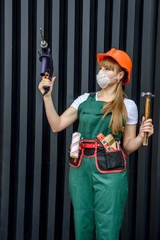 Garota com roupas de construção e equipamentos de proteção, posando com uma furadeira e um martelo na parede cinza.