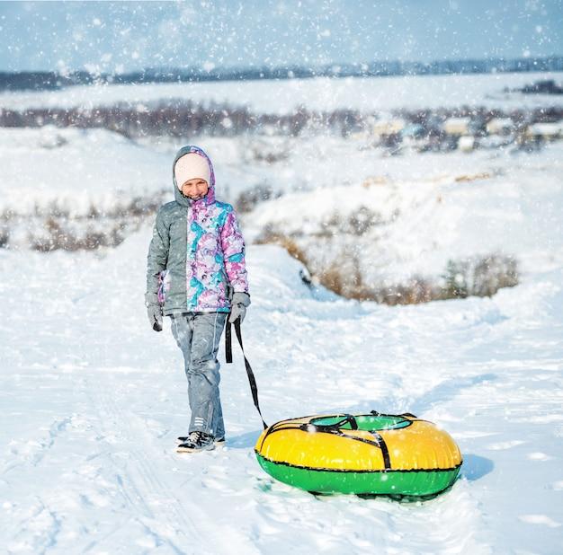 Garota com roupas de esqui arrasta neve tubulação na colina
