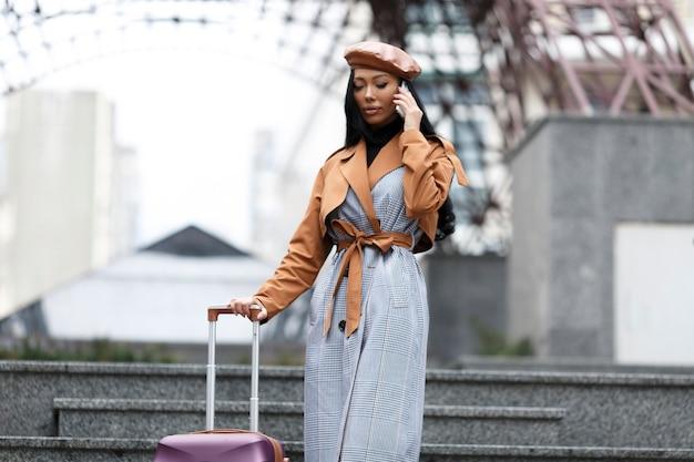 Garota com roupas de estilo francês segurando uma bolsa de viagem falando ao telefone, pronta para viajar