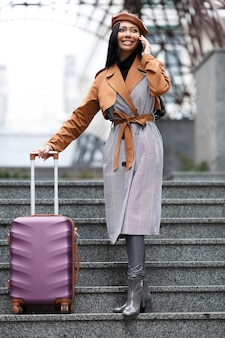 Garota com roupas de estilo francês segurando uma bolsa de viagem foto do conceito de viagens de pessoas