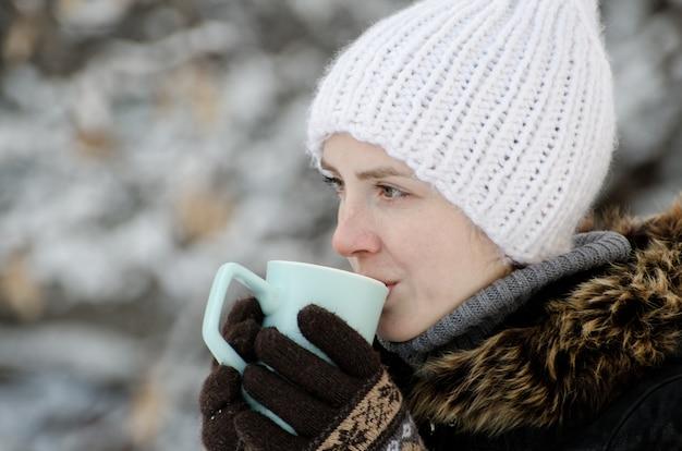 Garota com roupas de inverno, bebendo chá de uma caneca, vista lateral, close-up