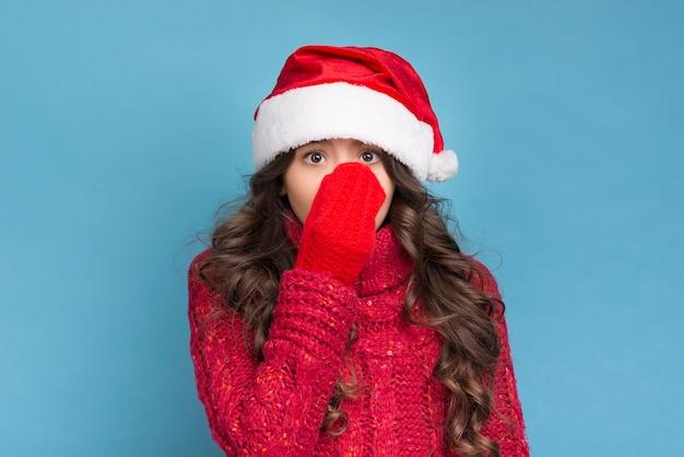 Garota com roupas de inverno, cobrindo o rosto com a mão