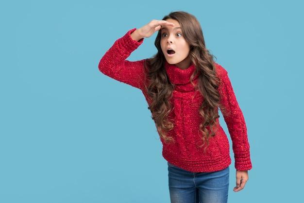 Garota com roupas de inverno com a mão na testa