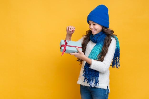Garota com roupas de inverno, desembalar um presente
