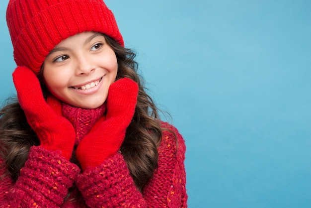 Garota com roupas de inverno vermelho, olhando para a esquerda