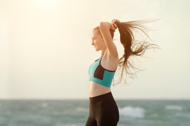 Garota com roupas esportivas na praia ajusta o cabelo dela. luz da manhã