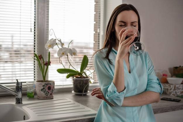 Garota com roupas para casa, bebendo um copo de vinho tinto. conceito de descanso depois do trabalho
