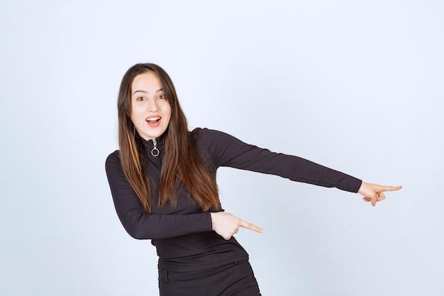 Garota com roupas pretas, apontando para algo à direita.