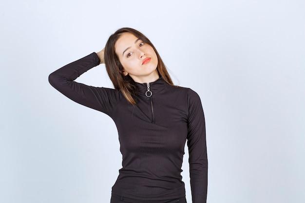 Garota com roupas pretas, dando poses profissionais e neutras sem reação.