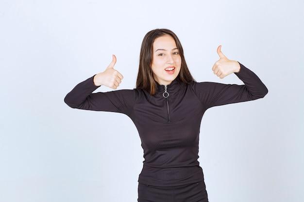 Garota com roupas pretas, mostrando o polegar para cima o sinal.