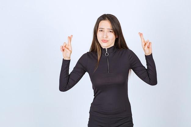 Garota com roupas pretas, mostrando o sinal da cruz de mão.