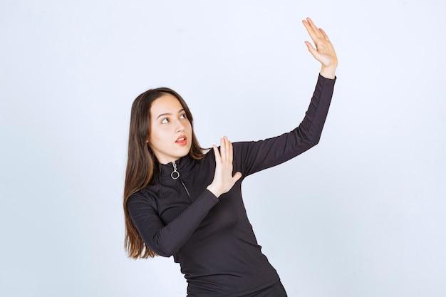 Garota com roupas pretas, tentando impedir alguma coisa.