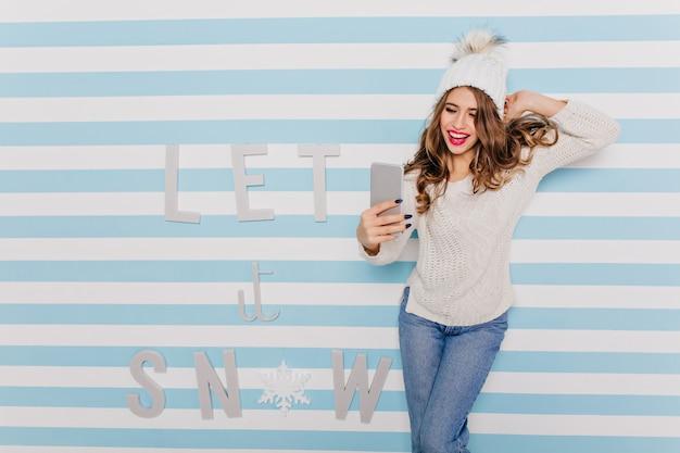 Garota com roupas quentes de inverno, mas elegantes, desafiadoramente olha para o telefone e posa para uma boa selfie contra inscrição de inverno