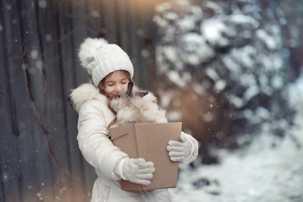 Garota com roupas quentes no inverno andando em montes de neve cobertos de neve