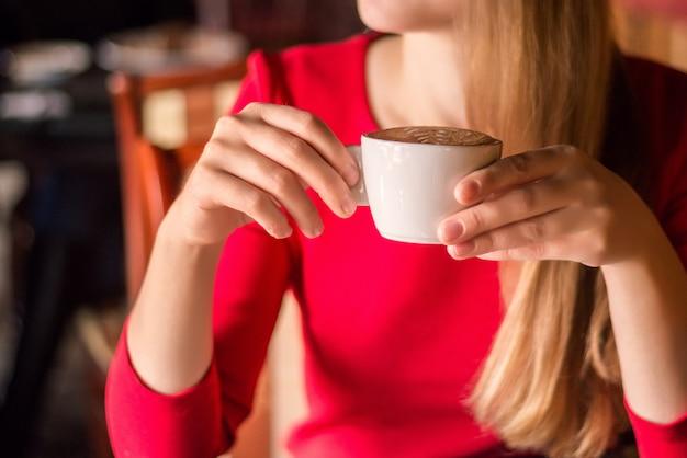 Garota com roupas vermelhas, tomando um café