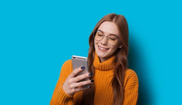 Garota com sardas está usando um telefone